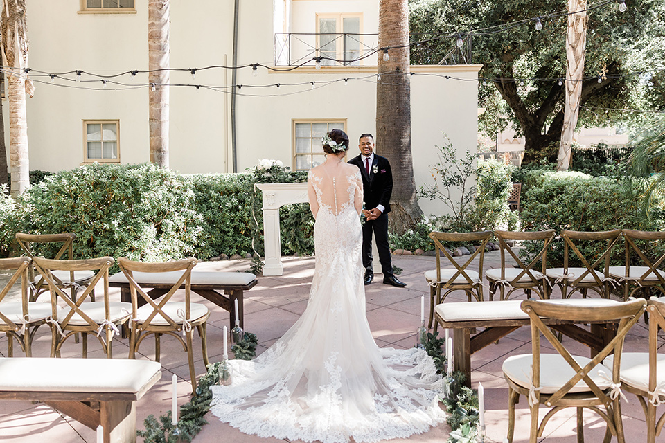 Maxwell-House-bride-walking-down-the-aisle-groom-waiting-bride-is-wearing-a-lace-long-sleeved-gown-groom-in-a-black-velvet-tuxedo