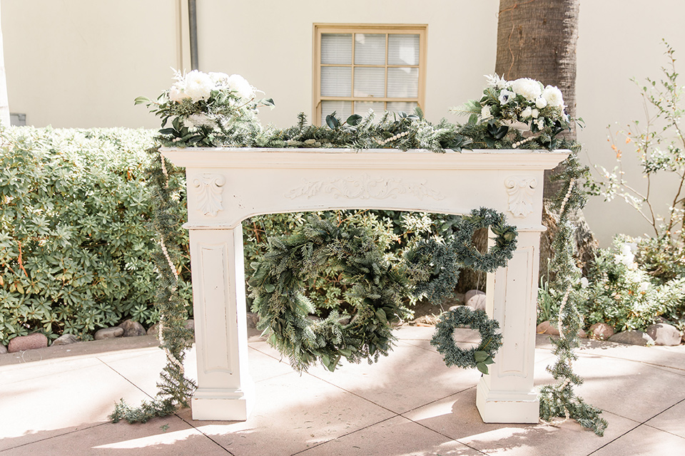 Maxwell-House-ceremony-set-up-with-a-white-firsplace-inspired-wedding-arch-with-greenery-and-florals
