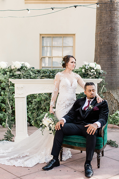 Maxwell-House-goom-sitting-in-a-chair-bride-standing-behind-them-bride-in-a-modern-lace-gown-groom-in-velvet-black-tuxedo