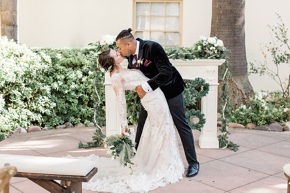 Maxwell-House-groom-dipping-bride-bride-is-wearing-a-lace-long-sleeved-gown-groom-in-a-black-velvet-tuxedo