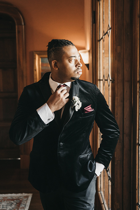 Maxwell-House-groom-looking-out-the-window-with-a-black-velvet-tuxedo-and-a-red-long-tie