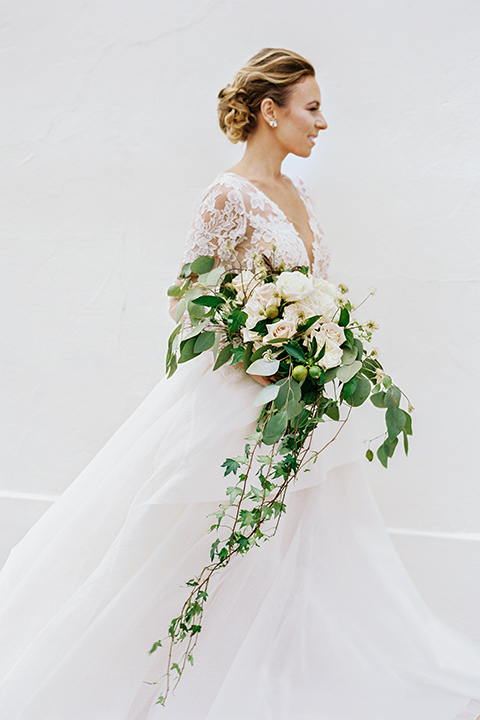 flower-market-shoot-bride-alone-walking-bride-in-a-flowing-tulle-ball-gown-with-lace-sleeves-and-hair-up