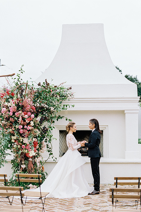 flower-market-shoot-brides-at-ceremony-space-bride-in-a-womens-black-shawl-lapel-tuxedo-with-polka-dot-bow-tie-bride-in-a-flowing-tulle-ball-gown-with-lace-sleeves-and-hair-up