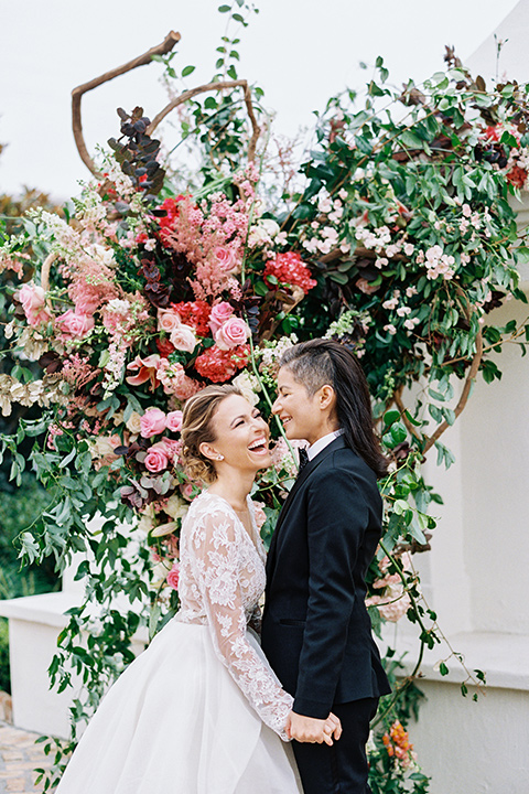 flower-market-shoot-brides-laughing-at-ceremony-bride-in-a-womens-black-shawl-lapel-tuxedo-with-polka-dot-bow-tie-bride-in-a-flowing-tulle-ball-gown-with-lace-sleeves-and-hair-up