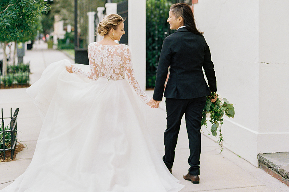 flower-market-shoot-brides-walking-away-from-camera-one-bride-in-a-flowing-tulle-gown-with-lace-sleeves-one-bride-in-a-blacl-shawl-lapel-tuxedo-with-a-polka-dot-bow