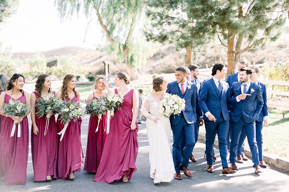 community-church-wedding-bridal-party-walking-bridesmaids-in-a-pink-berry-color-groomsmen-in-cobalt-suits-with-blue-ties-bride-in-a-flowing-gown-with-long-sleeves-and-an-illusion-bodice-groom-in-a-cobalt-blue-suit-with-a-berry-colored-tie