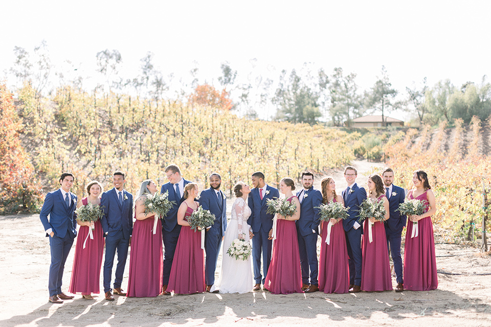 community-church-wedding-bridal-party-bridesmaids-in-a-pink-berry-color-groomsmen-in-cobalt-suits-with-blue-ties-bride-in-a-flowing-gown-with-long-sleeves-and-an-illusion-bodice-groom-in-a-cobalt-blue-suit-with-a-berry-colored-tie