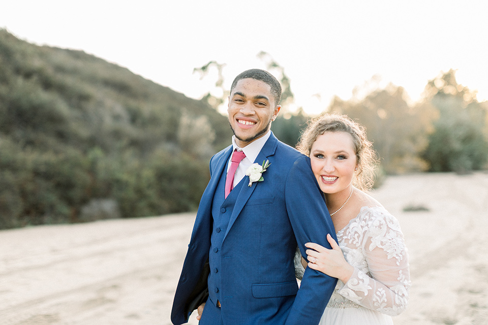 community-church-wedding-bride-and-groom-smiling-on-camera-bride-in-a-flowing-gown-with-long-sleeves-and-an-illusion-bodice-groom-in-a-cobalt-blue-suit-with-a-berry-colored-tie