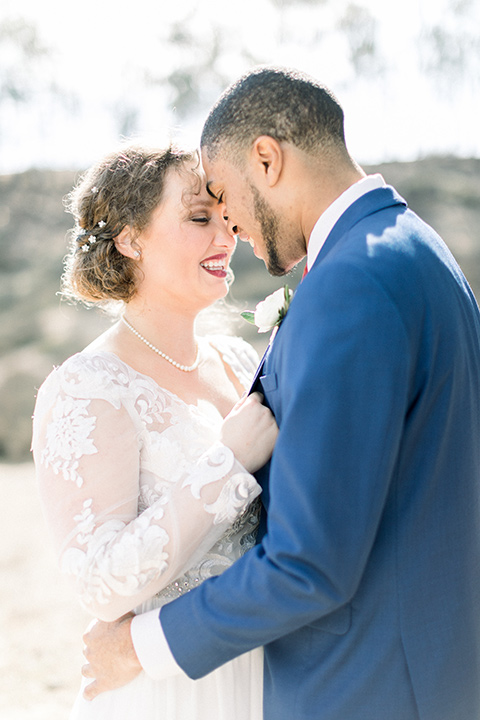 community-church-wedding-bride-and-groom-touching-heads-bride-in-a-flowing-gown-with-long-sleeves-and-an-illusion-bodice-groom-in-a-cobalt-blue-suit-with-a-berry-colored-tie