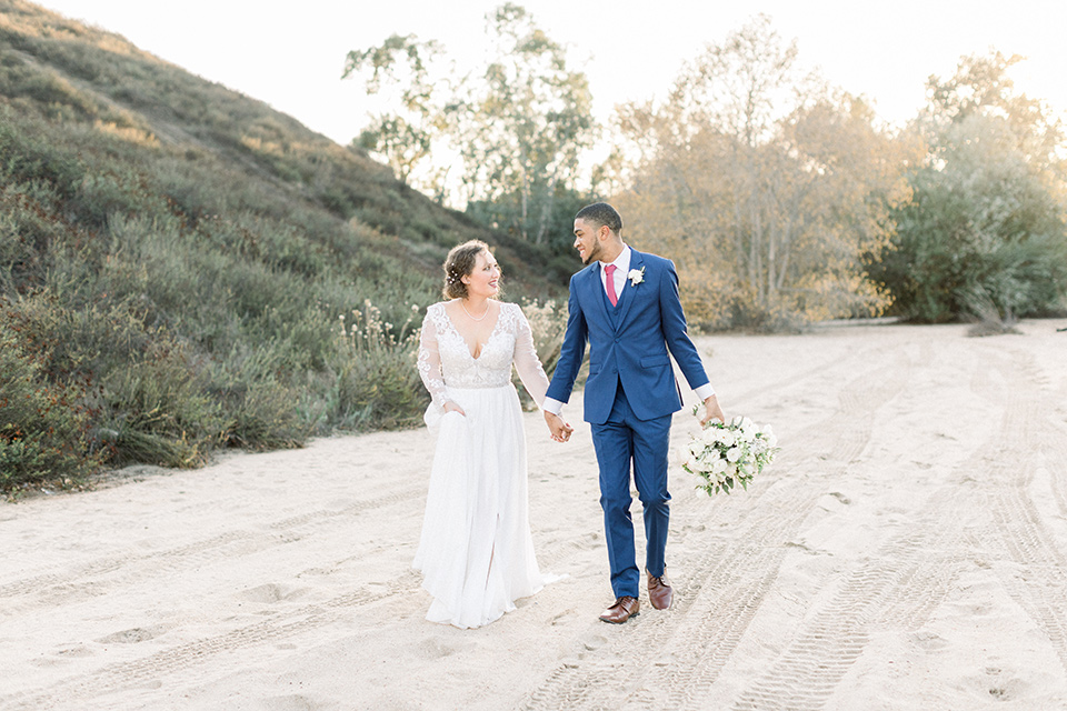 comminuty-church-wedding-bride-and-groom-walking-bride-in-a-flowing-gown-with-long-sleeves-and-an-illusion-bodice-groom-in-a-cobalt-blue-suit-with-a-berry-colored-tie