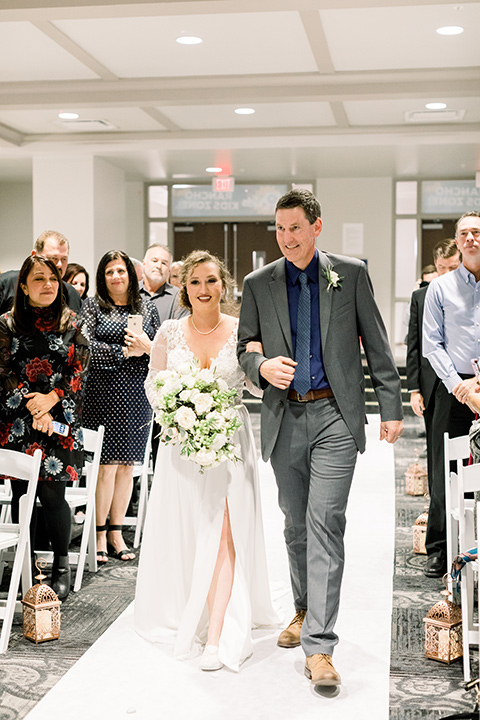 community-church-wedding-bride-walking-down-aisle-bride-in-a-flowing-gown-with-long-sleeves-and-an-illusion-bodice-groom-in-a-cobalt-blue-suit-with-a-berry-colored-tie