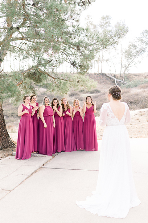 community-church-wedding-bridesmaids-seeing-bride-for-the-first-time-bride-in-a-flowing-boho-style-dress-with-sleeves-bridesmaids-in-berry-colored-dresses