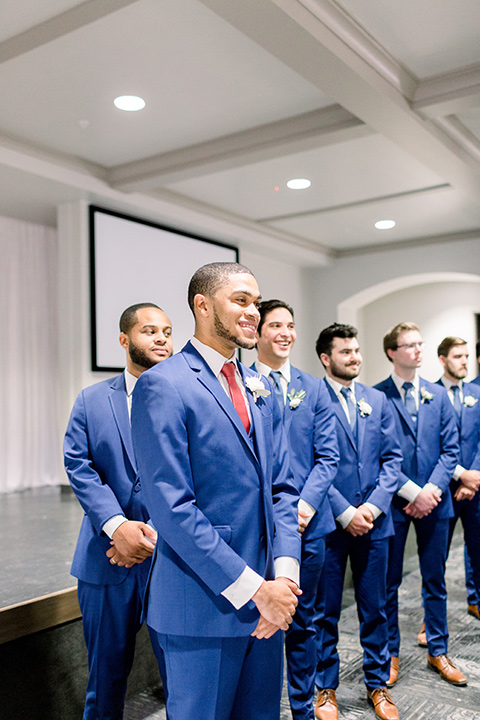 community-church-wedding-groom-at-end-of-aisle-waiting-groom-in-a-royal-blue-suit-with-berry-tie