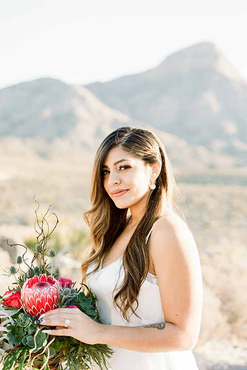 red-rocks-shoot-bride-alone-bride-in-a-flowing-white-gown-groom-in-a-grey-suit