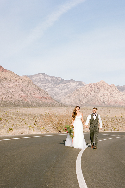 red-rocks-shoot-bride-and-groom-walking-in-the-street-bride-in-a-flowing-white-gown-groom-in-a-grey-suit
