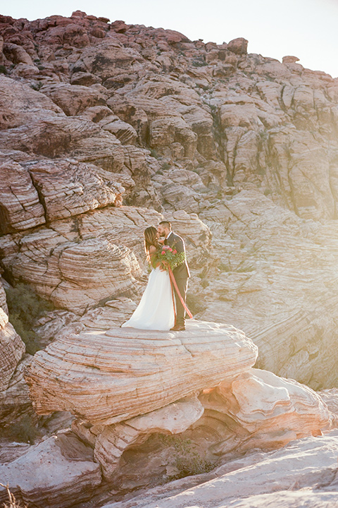 red-rocks-shoot-couple-on-rock-bride-in-a-flowing-white-gown-groom-in-a-grey-suit
