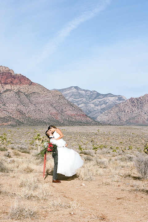 red-rocks-shoot-groom-holding-up-bride-bride-in-a-flowing-white-gown-groom-in-a-grey-suit