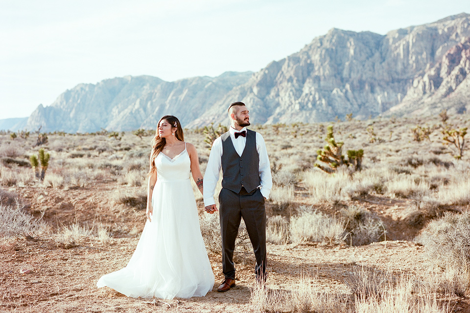 red-rocks-shoot-looking-away-bride-in-a-flowing-white-gown-groom-with-grey-suit