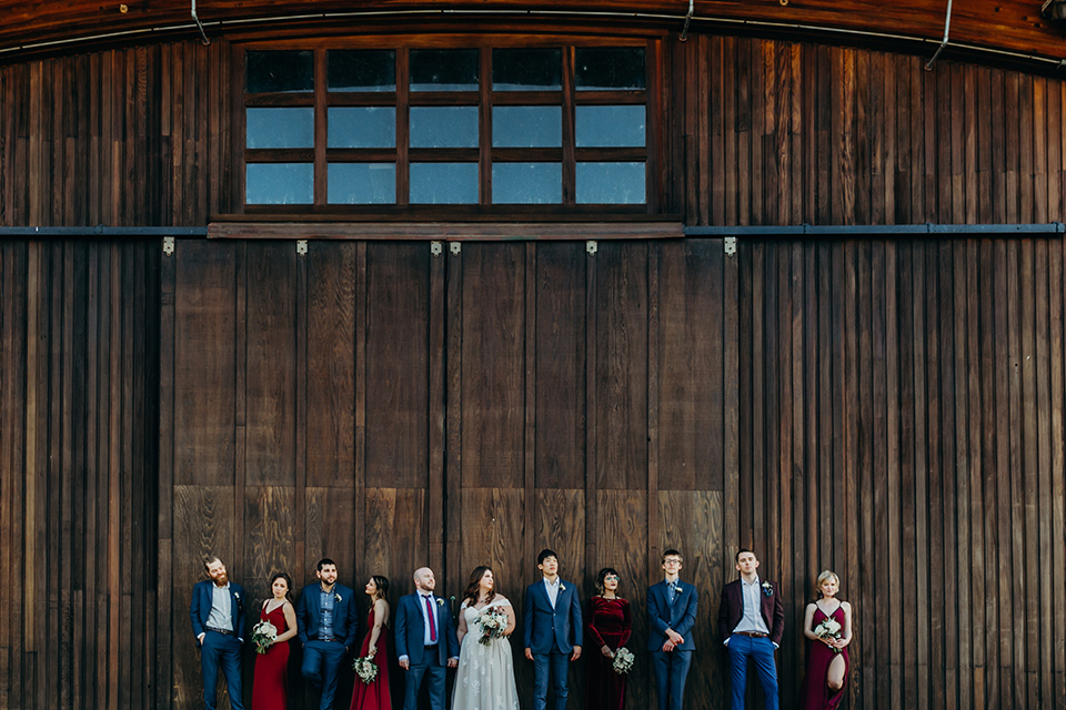 la-jolla-wedding-bridal-party-waist-up-photo-by-barn-bridesmaids-in-deep-red-dresses-groomsmen-in-dark-blue-suits-bride-in-a-flowing-ball-gown-with-a-detailed-bodice-and-straps-groom-in-a-dark-blue-suit-with-a-light-blue-suit-and-red-tie