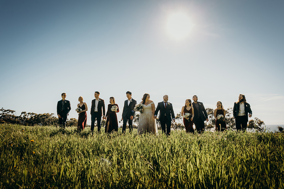 la-jolla-wedding-bridal-party-walking-in-grass-in-deep-red-dresses-groomsmen-in-dark-blue-suits-bride-in-a-flowing-ball-gown-with-a-detailed-bodice-and-straps-groom-in-a-dark-blue-suit-with-a-light-blue-suit-and-red-tie