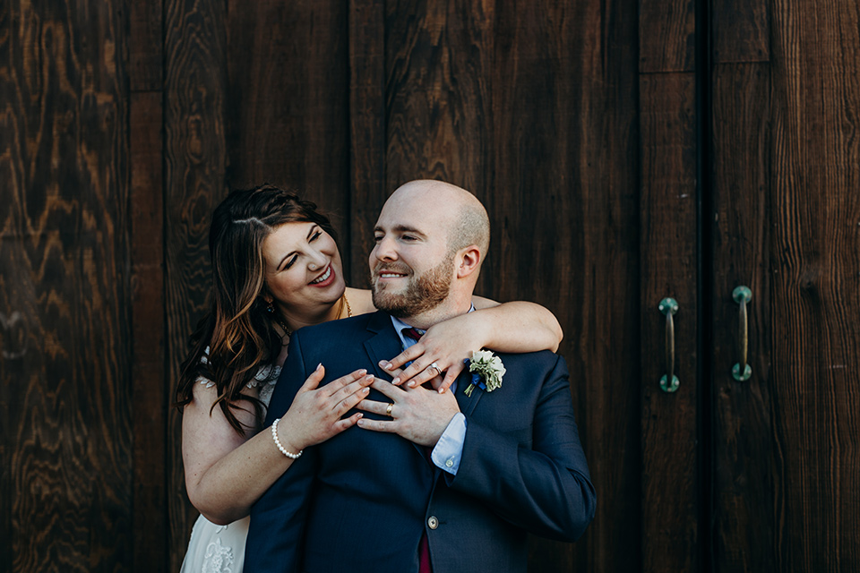 la-jolla-wedding-bride-and-groom-by-wooden-door-bride-in-a-flowing-ball-gown-with-a-detailed-bodice-and-straps-groom-in-a-dark-blue-suit-with-a-light-blue-suit-and-red-tie
