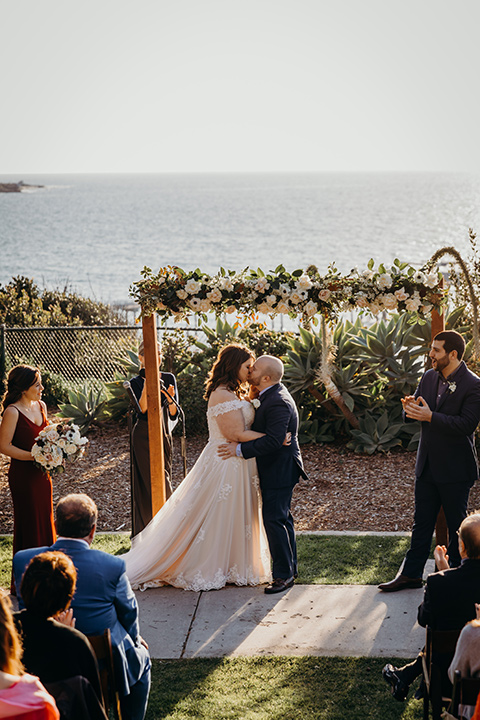 la-jolla-wedding-bride-and-groom-first-kiss-bride-in-a-tulle-ballgown-with-a-crystaled-bodice-and-cap-sleeves-groom-in-a-navy-suit-and-light-blue-shirt