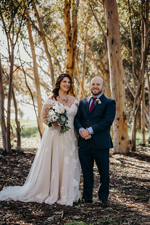 la-jolla-wedding-bride-and-groom-smiling-at-camera-by-trees-bride-in-a-tulle-ballgown-with-a-crystaled-bodice-and-cap-sleeves-groom-in-a-navy-suit-and-light-blue-shirt