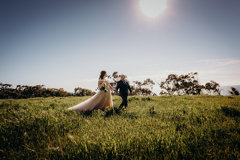 la-jolla-wedding-bride-and-groom-walking-in-grass-bride-in-a-flowing-ball-gown-with-a-detailed-bodice-and-straps-groom-in-a-dark-blue-suit-with-a-light-blue-suit-and-red-tie