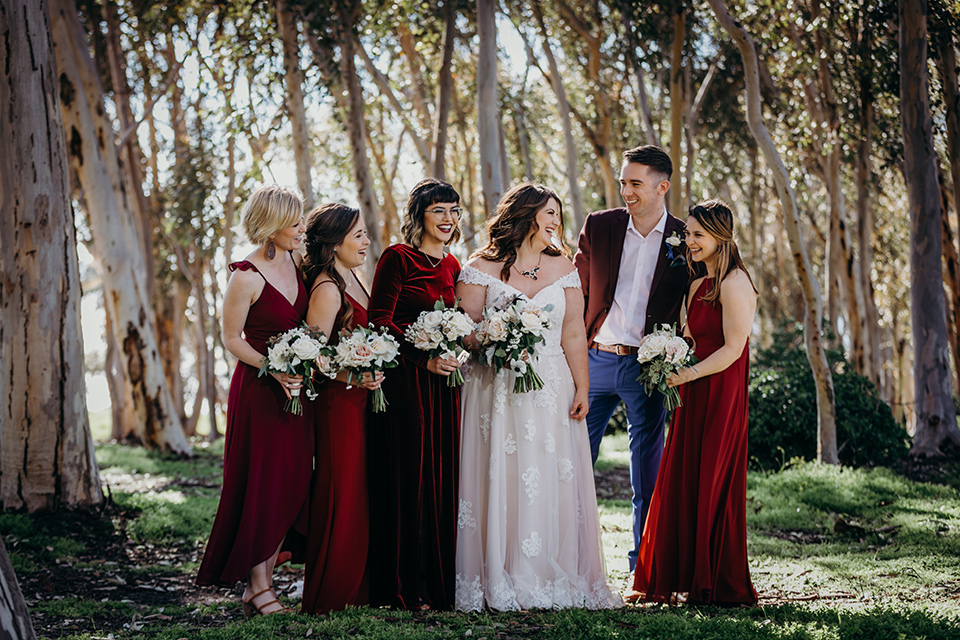la-jolla-wedding-bride-and-her-bridesmaids-and-bridesman-bride-in-a-flowing-ball-gown-with-a-detailed-bodice-and-straps-bridesmaids-in-dark-burgundy-red-dresses