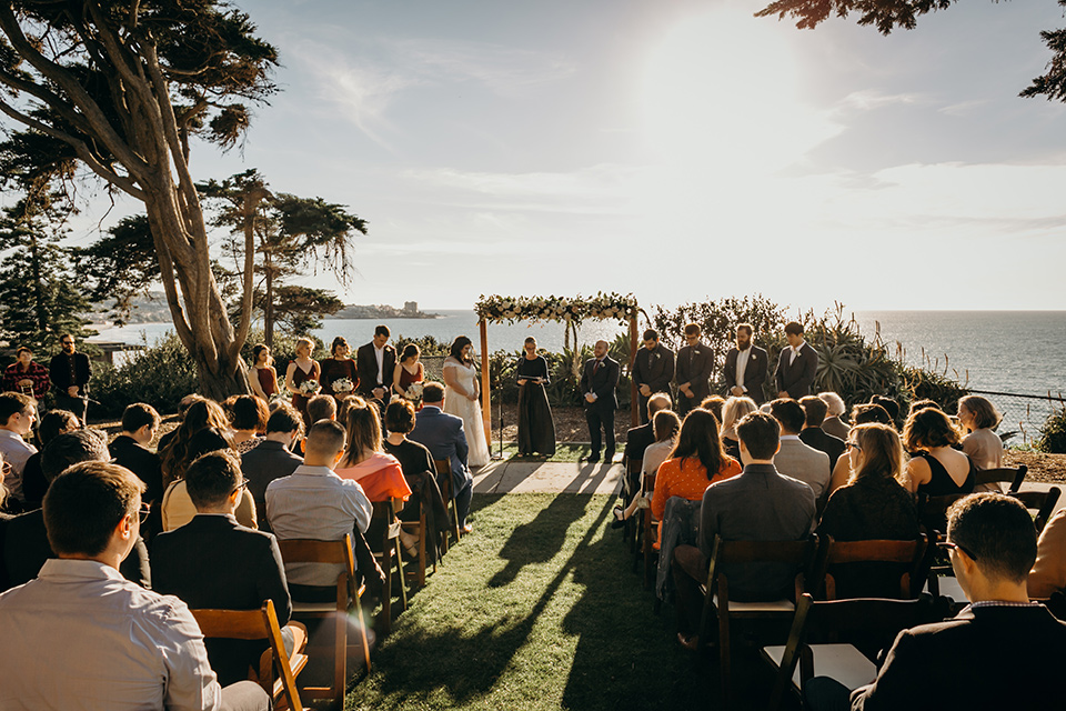 la-jolla-wedding-ceremony-bride-in-a-flowing-ball-gown-with-a-detailed-bodice-and-straps-groom-in-a-dark-blue-suit-with-a-light-blue-suit-and-red-tie