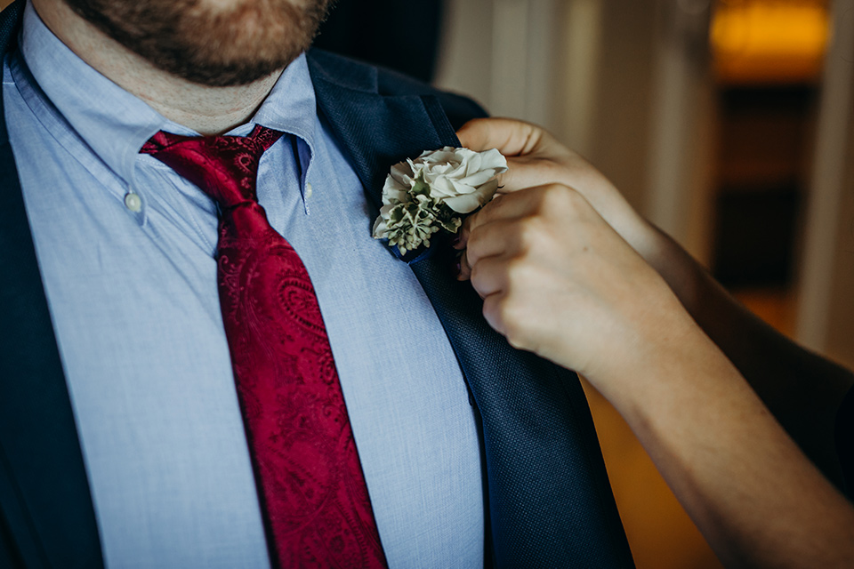 la-jolla-wedding-close-up-on-groom-attire-groom-in-a-dark-blue-suit-with-a-light-blue-suit-and-red-tie