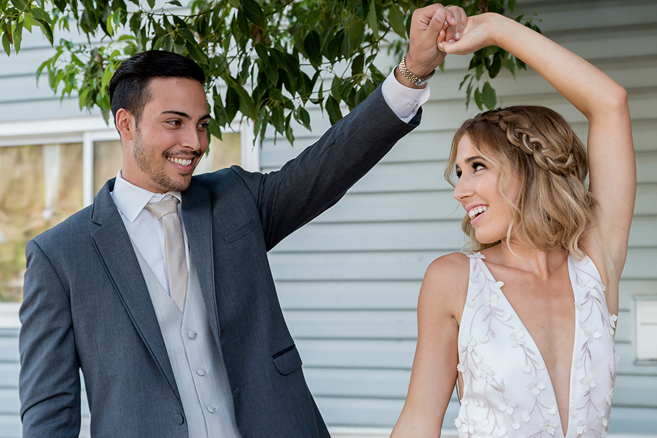 Blossom-valley-victorian-wedding-shoot-bride-and-groom-dancing-bride-weaing-a-flowing-gown-with-straps-and-groom-wore-a-mix-and-match-look-with-a-dark-grey-coat-and-light-grey-pants