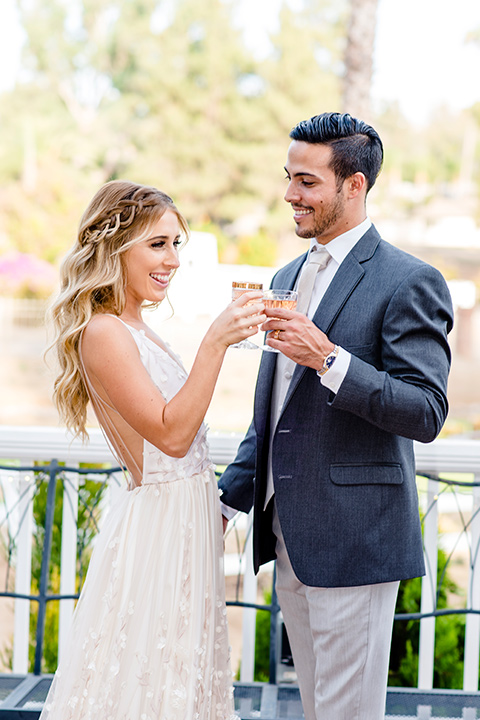 Blossom-valley-victorian-wedding-shoot-bride-and-groom-drinking-bride-wearing-a-tulle-ballgown-with-a-deep-v-and-groom-wearing-a-mix-and-match-look-with-light-grey-pants-and-a-dark-grey-coat