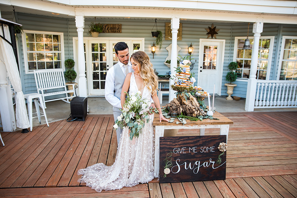 Blossom-valley-victorian-wedding-shoot-bride-and-groom-in-front-of-the-venue-bride-weaing-a-flowing-gown-with-straps-and-groom-wore-a-mix-and-match-look-with-a-dark-grey-coat-and-light-grey-pants