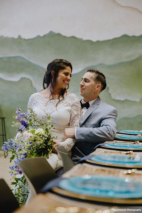 gather-venues-bride-sitting-on-grooms-lap-bride-in-a-lace-gown-groom-in-a-light-blue-suit