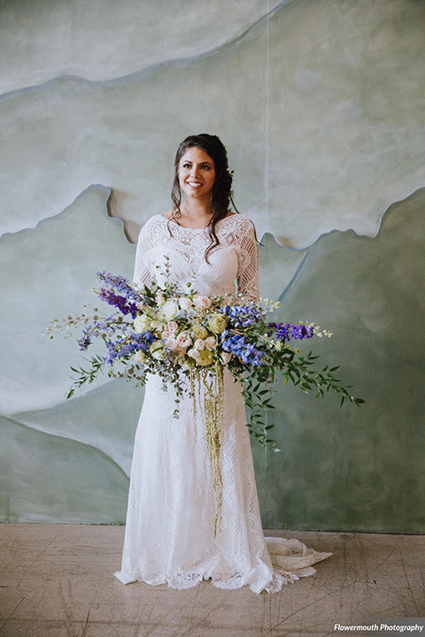 gather-venues-bride-alone-bride-iswearing-a-fitted-lace-dress-with-long-sleeves-and-a-high-neckline-with-a-big-floral-bouquet