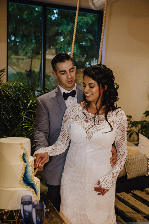 gather-venues-cutting-the-cake-groom-in-light-blue-suit-and-dark-blue-pants-bride-in-a-fitted-lace-gown