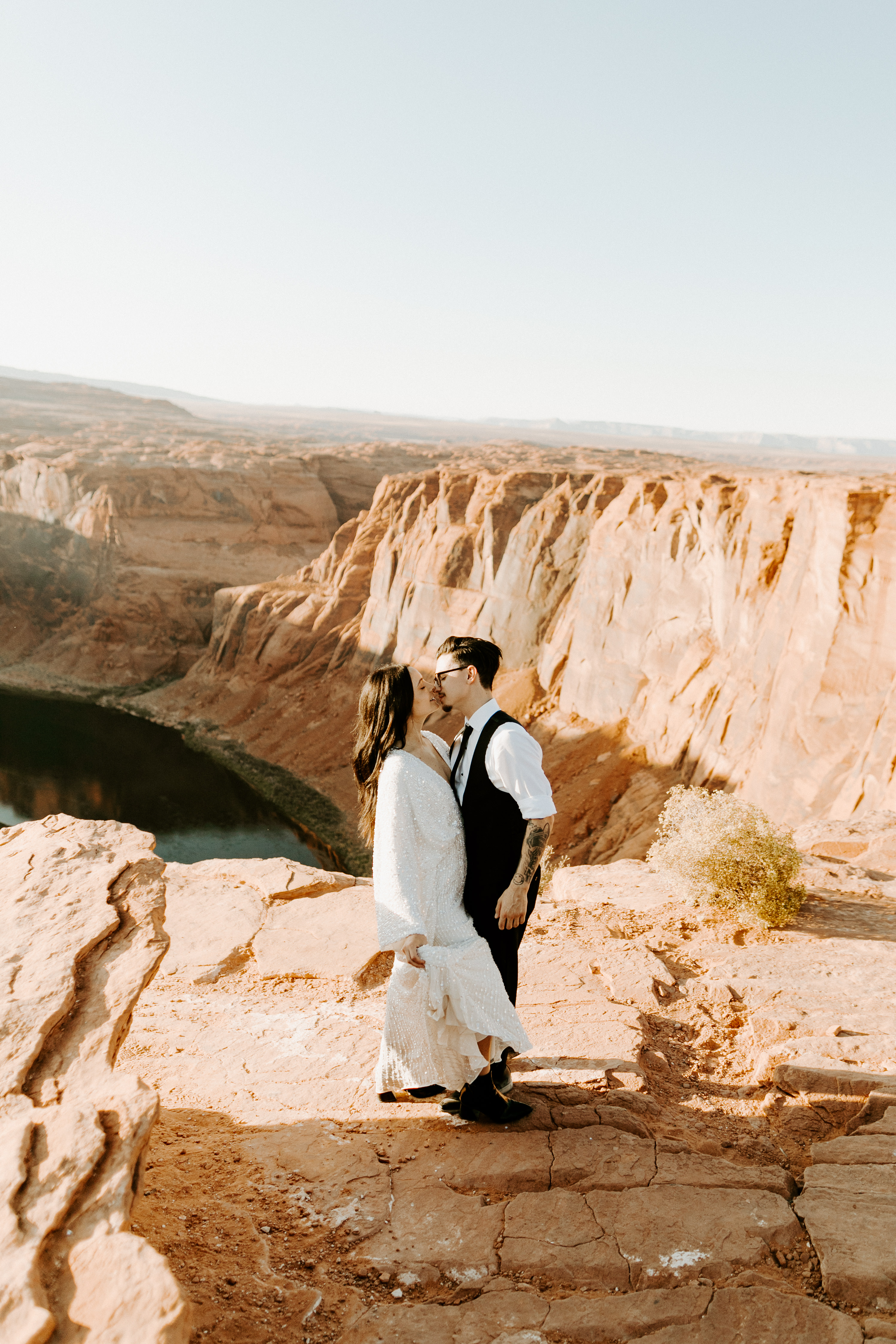 bride in an ivory long gown with bellowing sleeves and a boho design, groom in a black double-breasted vest and a white buttoned up shirt
