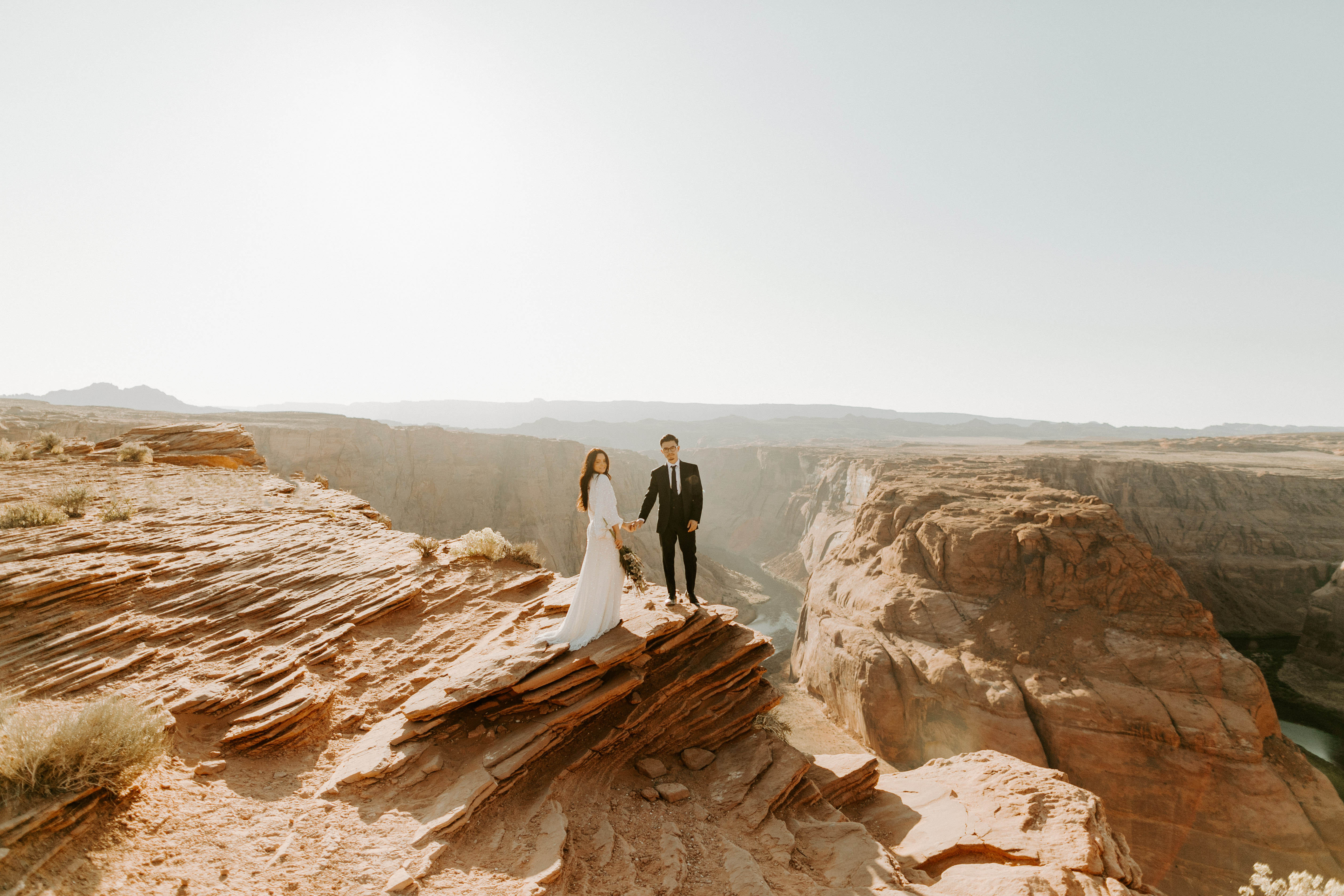 bride in an ivory long gown with bellowing sleeves and a boho design, groom in a black double-breasted vest and a white buttoned up shirt standing on horseshoe bend