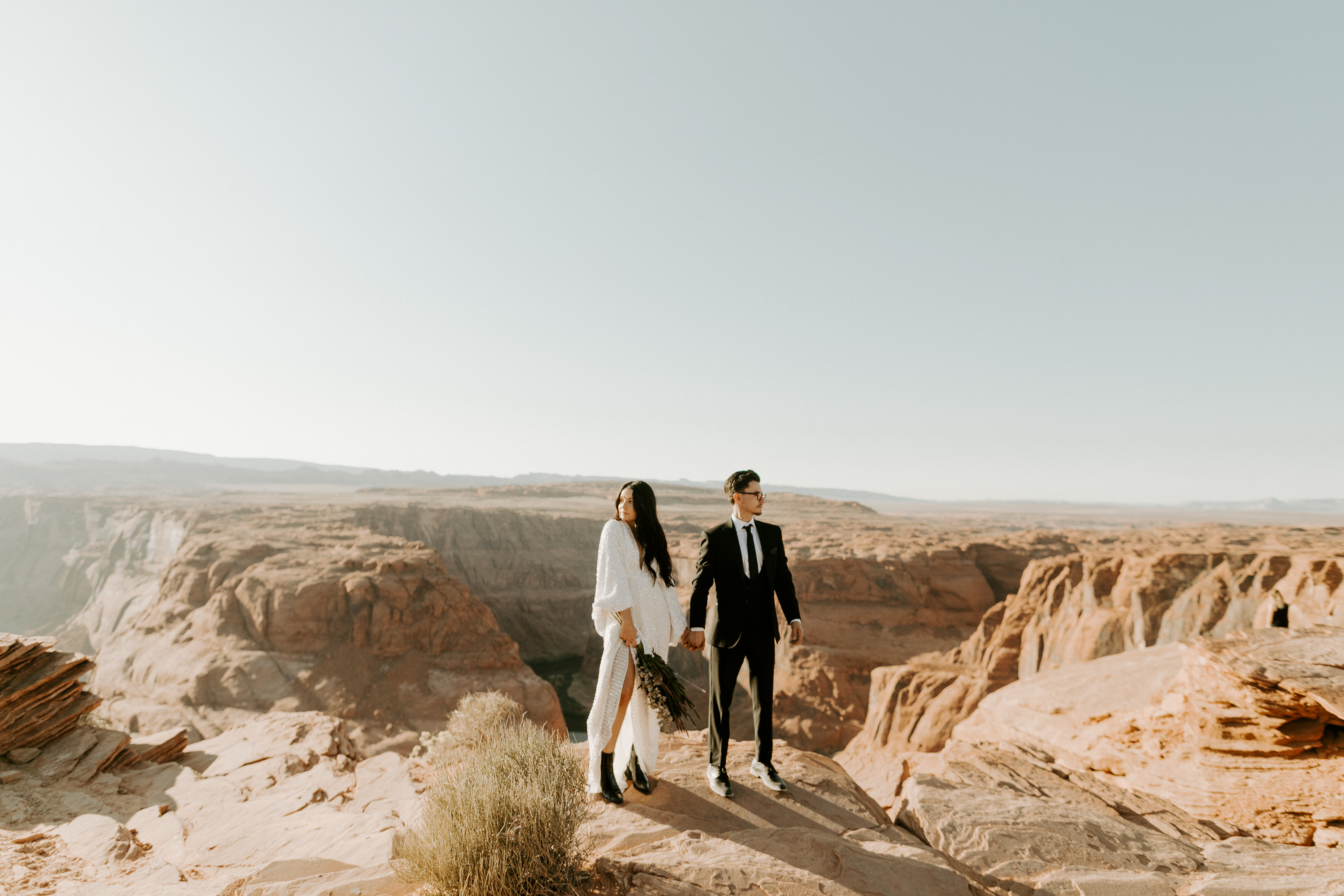 bride in an ivory long gown with bellowing sleeves and a boho design, groom in a black double-breasted vest and a white buttoned up shirt walking on horseshoe bend