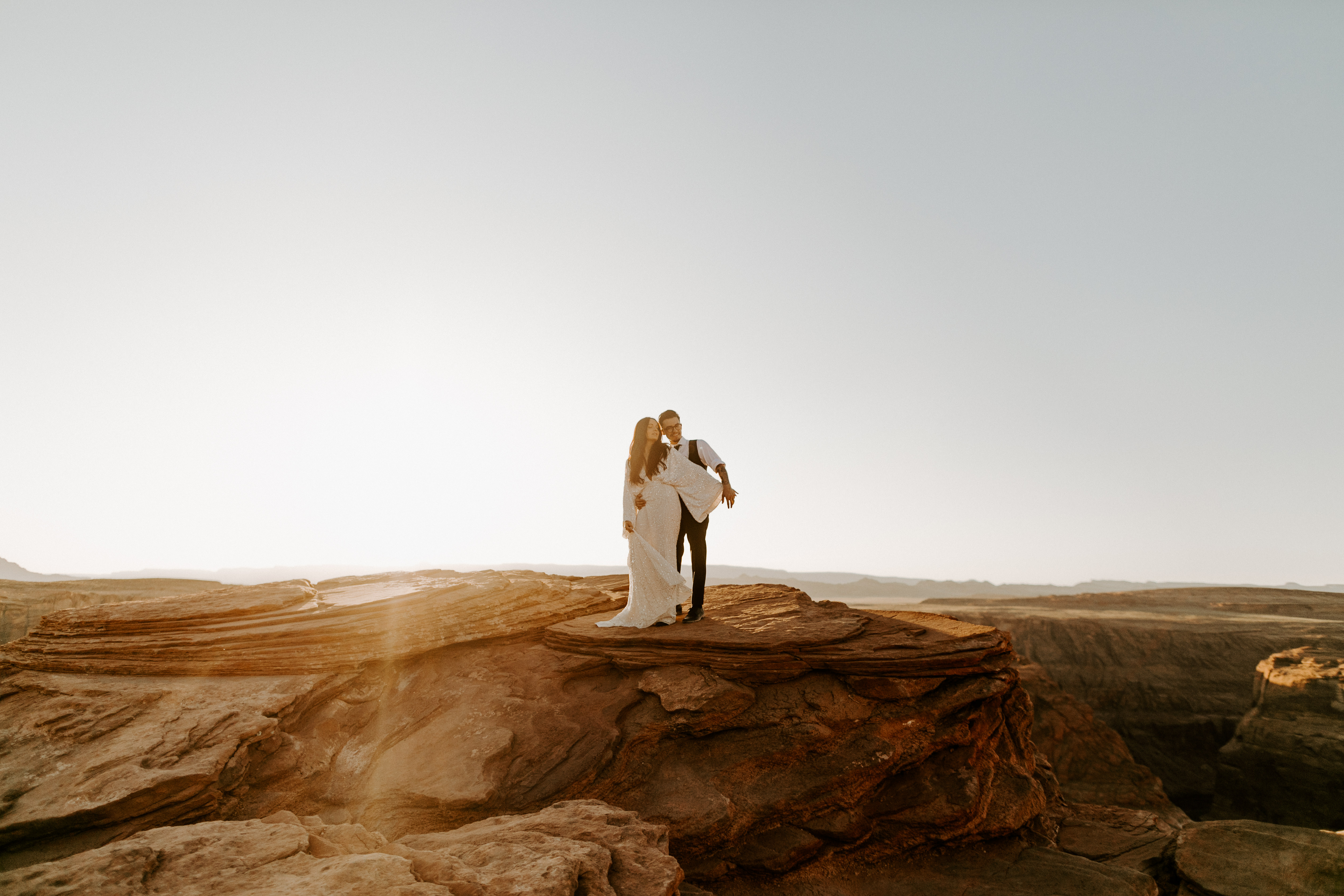 bride in an ivory long gown with bellowing sleeves and a boho design, groom in a black double-breasted vest and a white buttoned up shirt walking on horseshoe bend and cliffs