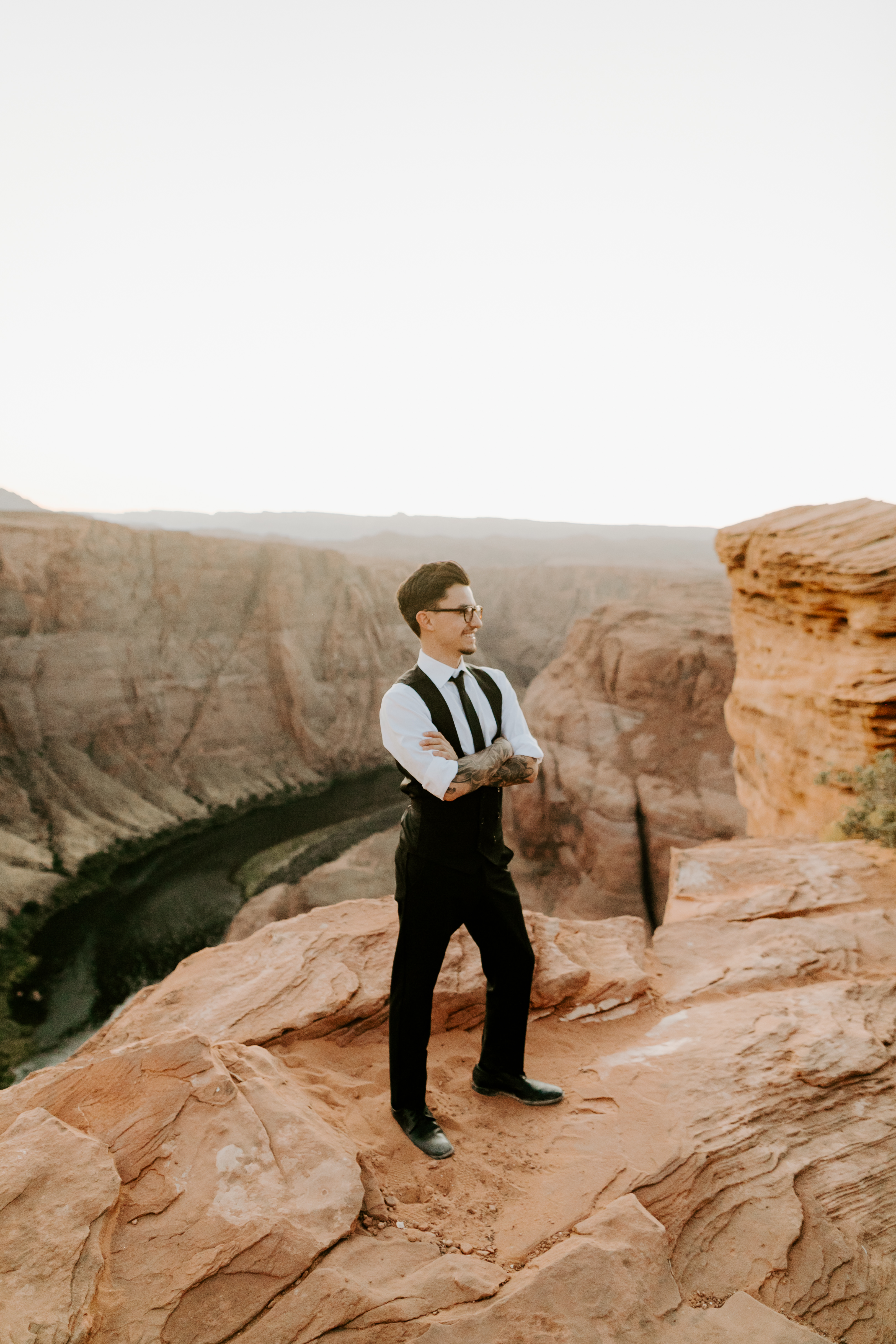 groom in a black double-breasted vest and a white buttoned up shirt sitting on cliffside