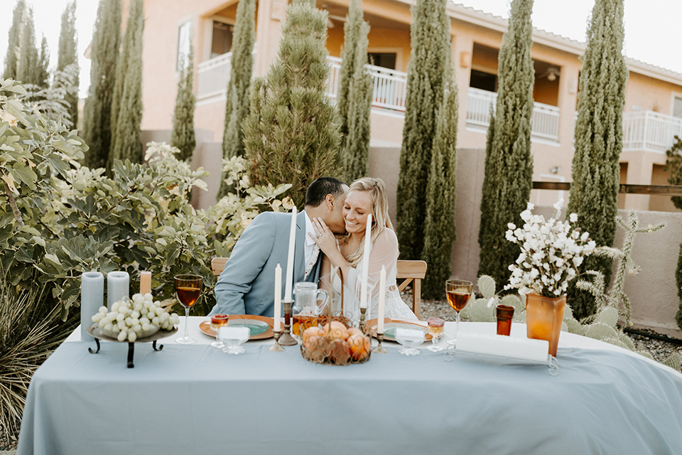 bride and groom sitting at sweetheart table, bride in an ivory lace gown with bellowing sleeves and a boho design.  The groom is in a light blue suit with matching vest and no tie