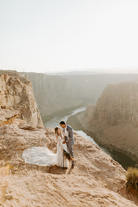 bride in an ivory lace gown with bellowing sleeves and a boho design, The groom is in a light blue suit with matching vest and no tie