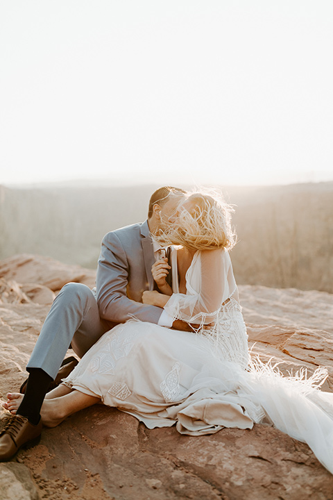 bride in an ivory lace gown with bellowing sleeves and a boho design, The groom is in a light blue suit with matching vest and no tie resting on the side of the cliff