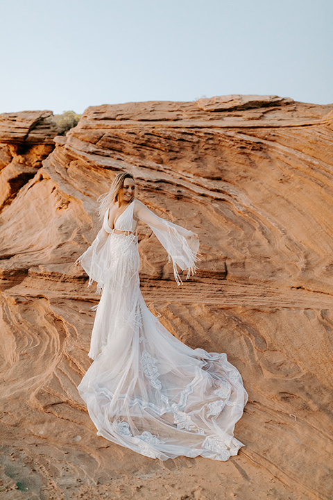 bride in an ivory lace gown with bellowing sleeves and a boho design standing