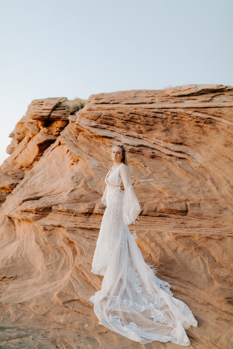 bride in an ivory lace gown with bellowing sleeves and a boho design resting on the side of the cliff