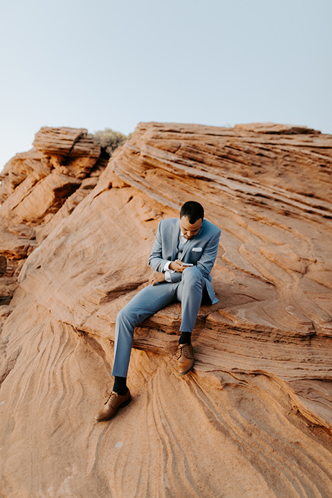 The groom is in a light blue suit with matching vest and no tie sitting on the side of the cliff