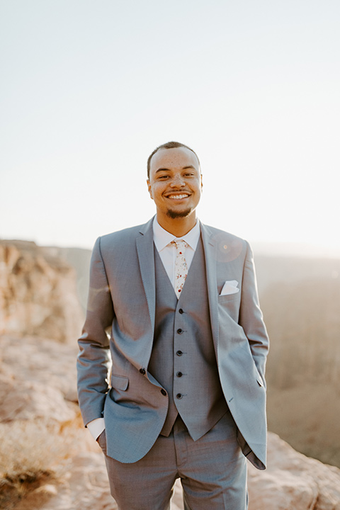 The groom is in a light blue suit with matching vest and no tie resting on the side of the cliff
