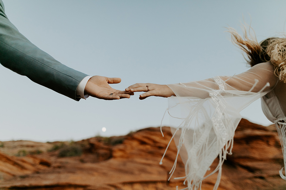 bride and groom standing on cliff in a faraway shot, bride in an ivory lace gown with bellowing sleeves and a boho design.  The groom is in a light blue suit with matching vest and no tie